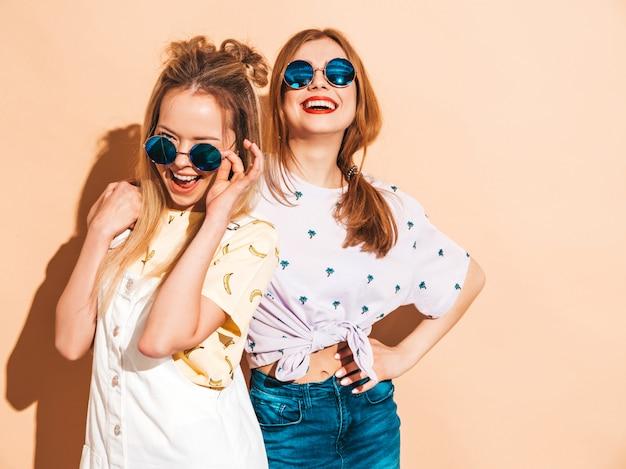 Twee jonge mooie glimlachende blonde hipstermeisjes in kleren van de trendy de zomer kleurrijke t-shirt. Gratis Foto