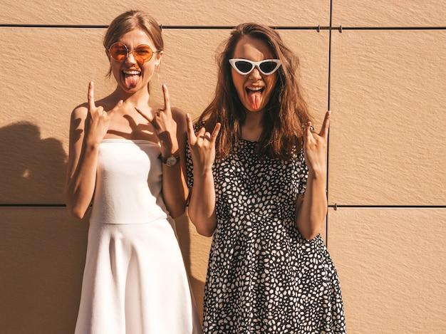 Twee jonge mooie glimlachende hipster meisjes in trendy zomerjurk. Gratis Foto