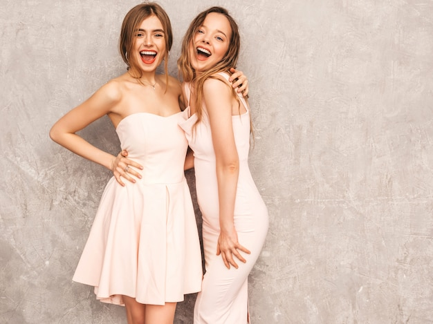 Twee jonge mooie glimlachende meisjes in trendy zomer lichtroze jurken. sexy zorgeloze vrouwen poseren. positieve modellen hebben plezier Gratis Foto