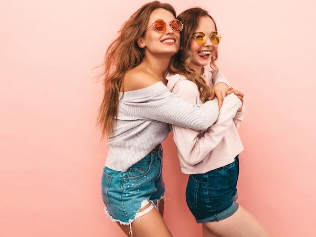 Twee jonge mooie glimlachende meisjes in trendy zomerkleren. sexy zorgeloze vrouwen poseren. positieve modellen hebben plezier Gratis Foto