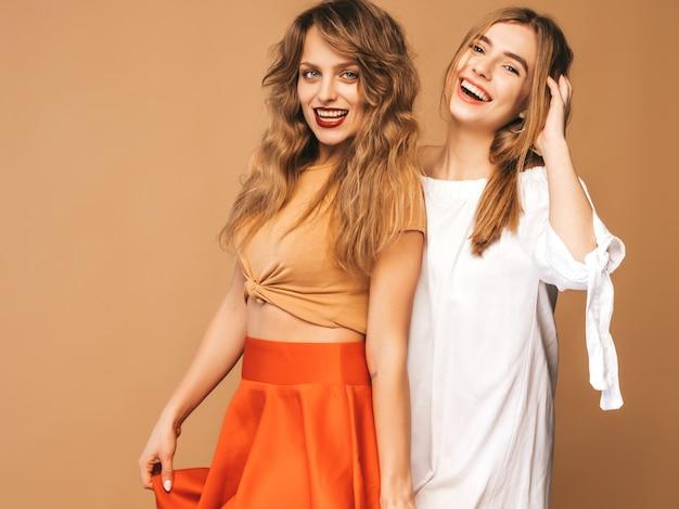 Twee jonge mooie glimlachende meisjes in trendy zomerkleren. sexy zorgeloze vrouwen poseren. positieve modellen Gratis Foto