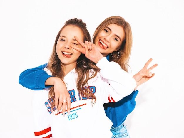 Twee jonge mooie glimlachende meisjes in trendy zomerkleren. sexy zorgeloze vrouwen. positieve modellen die vredesteken tonen Gratis Foto