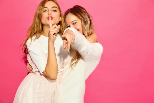 Twee jonge mooie glimlachende vrouwen in trendy zomer witte kleren Gratis Foto