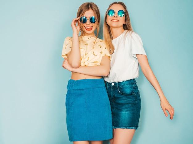 Twee jonge mooie lachende blonde hipster meisjes in trendy zomer jeans rokken kleding. Gratis Foto