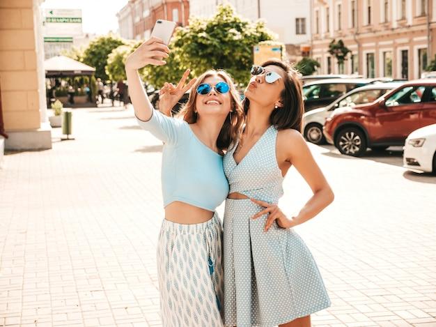 Twee jonge mooie lachende hipster meisjes in trendy zomerkleding. sexy zorgeloze vrouwen die zich voordeed op de straat achtergrond in zonnebril. ze nemen selfie-zelfportretfoto's op smartphone bij zonsondergang Gratis Foto