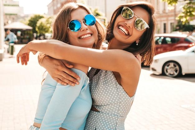 Twee jonge mooie lachende hipster meisjes in trendy zomerkleding. sexy zorgeloze vrouwen die zich voordeed op straat achtergrond in zonnebril. positieve modellen die plezier hebben en knuffelen Gratis Foto