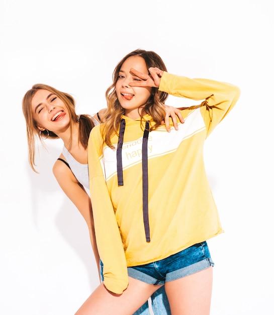Twee jonge mooie lachende meisjes in trendy zomer jeans kleding en gele hoodie. zorgeloze vrouwen. positieve modellen Gratis Foto