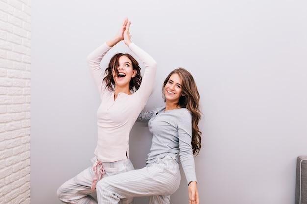 Twee jonge mooie meisjes in nachtpyjama's die binnen op grijze muur pret hebben. meisje met krullend haar probeert yoga te doen. Gratis Foto