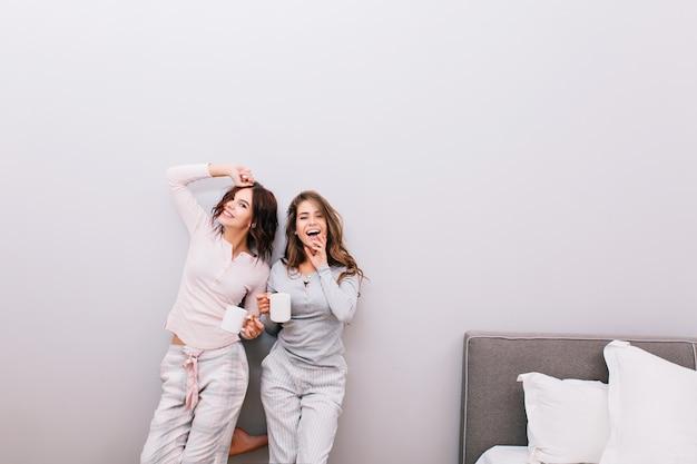 Twee jonge mooie meisjes in nachtpyjama's met kopjes plezier in slaapkamer op grijze muur. Gratis Foto