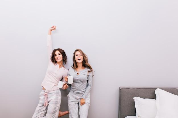 Twee jonge mooie meisjes in pyjama's met cups in slaapkamer op grijze muur. ze hebben plezier en glimlachen. Gratis Foto