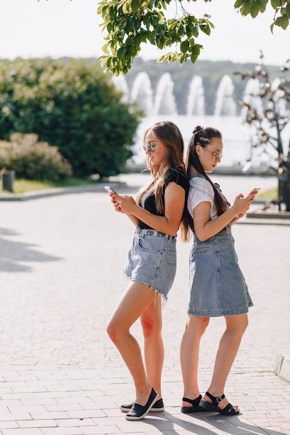 Twee jonge mooie meisjes op een wandeling in het park met telefoons Gratis Foto