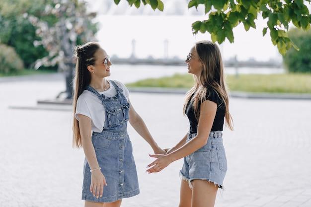 Twee jonge mooie meisjes op een wandeling in het park of op straat Gratis Foto