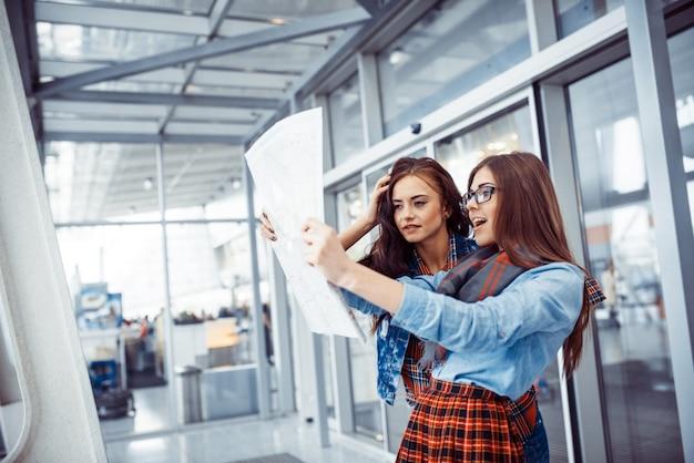 Twee jonge mooie meisjes studeren en kijken naar de kaart. Premium Foto