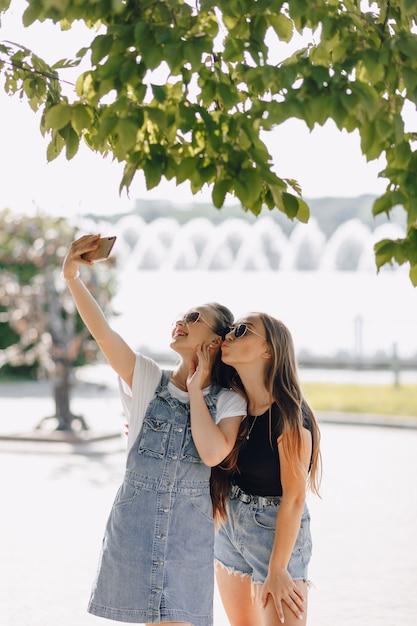 Twee jonge mooie meisjes tijdens een wandeling in het park die foto's van zichzelf aan de telefoon nemen Gratis Foto