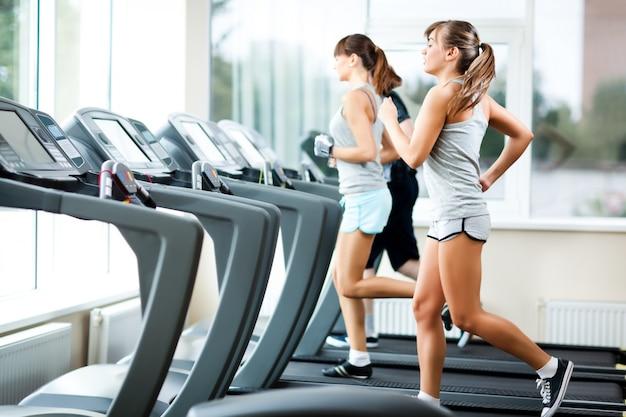 Twee jonge mooie slanke vrouwen in sportkleding draait op loopbanden in de sportschool Premium Foto