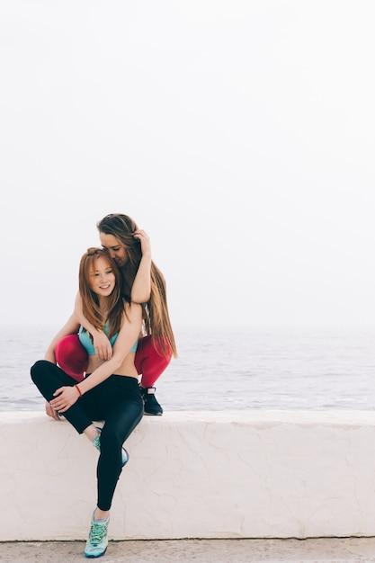 Twee jonge mooie vriendinnen zittend op de achtergrond van de zee Premium Foto