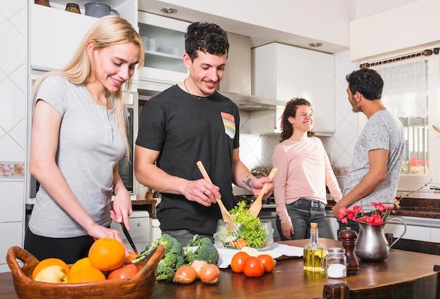 Twee jonge paren die samen voedsel in de keuken voorbereiden Gratis Foto
