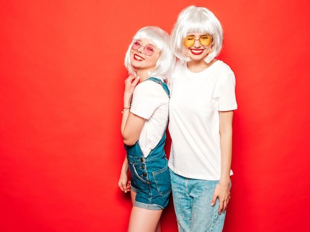 Twee jonge sexy lachende hipster meisjes in witte pruiken en rode lippen. mooie trendy vrouwen in de zomer kleding. zorgeloze modellen poseren in de buurt van rode muur in studio zomer gek Gratis Foto