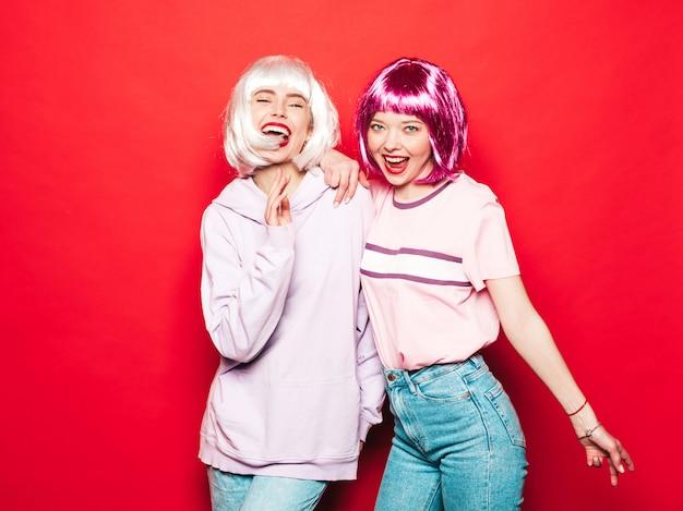 Twee jonge sexy lachende hipster meisjes in witte pruiken en rode lippen. mooie trendy vrouwen in zomer kleding. zorgeloze modellen poseren in de buurt van rode muur in studio gek Gratis Foto