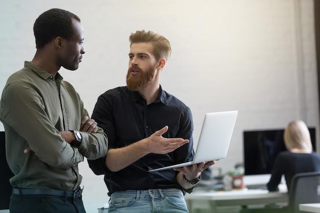 Twee jonge slimme bedrijfsmensen die nieuw project bespreken Gratis Foto