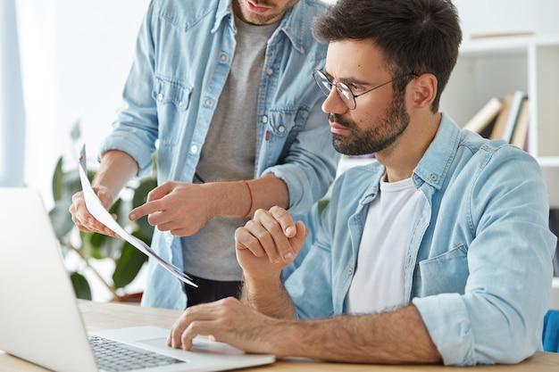 Twee jonge succesvolle ondernemers werken samen in coworking space Gratis Foto