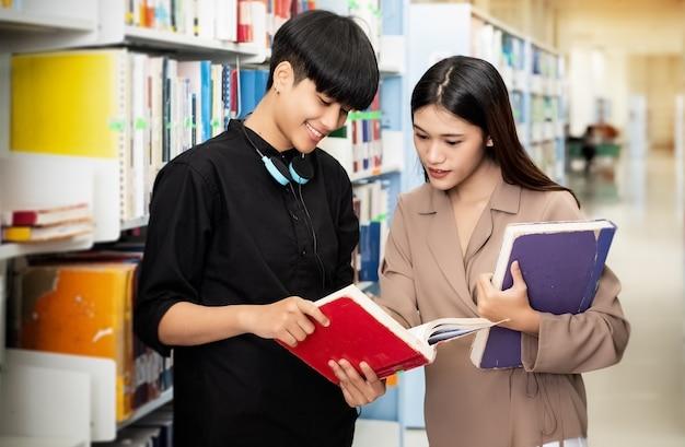 Twee jonge tieners praten en lezen boek samen, zoeken naar gegevens voor examen, bij bibliotheek, wazig licht rond Premium Foto