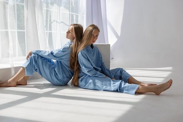 Twee jonge tweelingmeisjes in identieke blauwe pakken zittend op witte cyclorama vloer in de studio Premium Foto