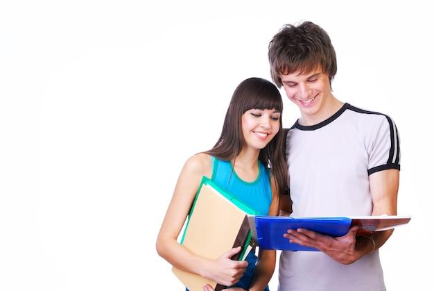 Twee jonge volwassen studenten die zich dichtbij en lezen bevinden Gratis Foto