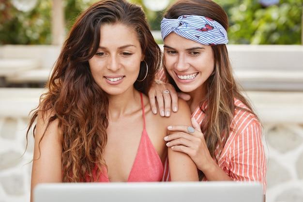 Twee jonge vrouwelijke modellen zitten voor geopende draagbare laptop, kijken naar online uitzendingen en glimlachen vrolijk, steunen elkaar. Gratis Foto