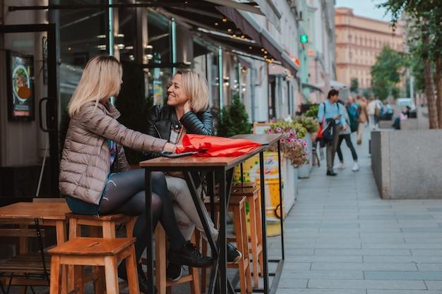 Twee jonge vrouwelijke vrienden ontmoetten elkaar in een café in de straat en hebben plezier bij het chatten. Premium Foto