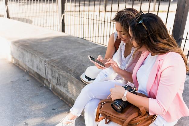 Twee jonge vrouwen die dichtbij het traliewerk zitten die mobiele telefoon bekijken Gratis Foto