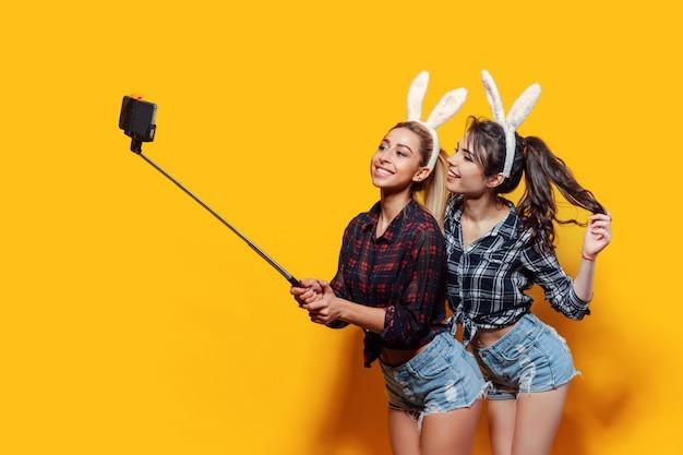 Twee jonge vrouwen die leuke pasen-konijnoren dragen en selfie gebruikend stok maken Premium Foto
