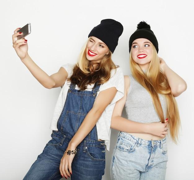 Twee jonge vrouwen die selfie met mobiele telefoon nemen Premium Foto