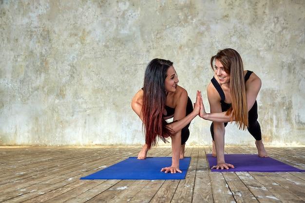 Twee jonge vrouwen doen gepaarde oefeningen in de fitnessruimte. poseren en glimlachen naar de camera, veel plezier, geweldige sfeer. Premium Foto