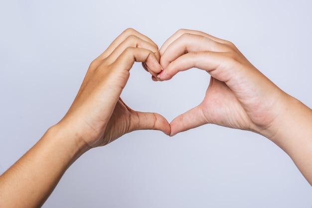 Twee jonge vrouwen houden van elkaar handteken hartvorm. Gratis Foto