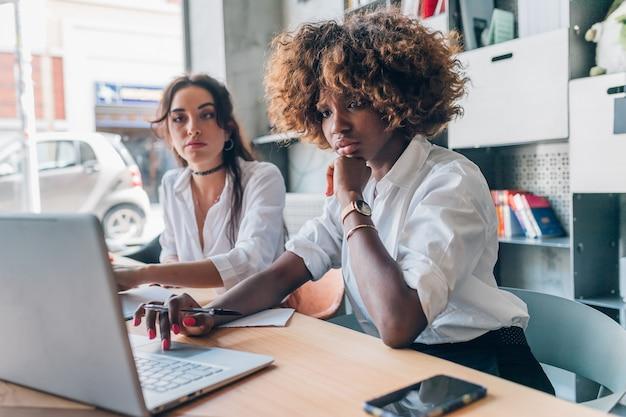 Twee jonge vrouwen van het creatieve team binnen werken Premium Foto