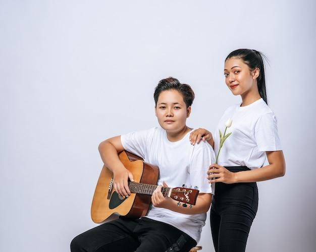 Twee jonge vrouwen zaten op een stoel en speelden gitaar. Gratis Foto