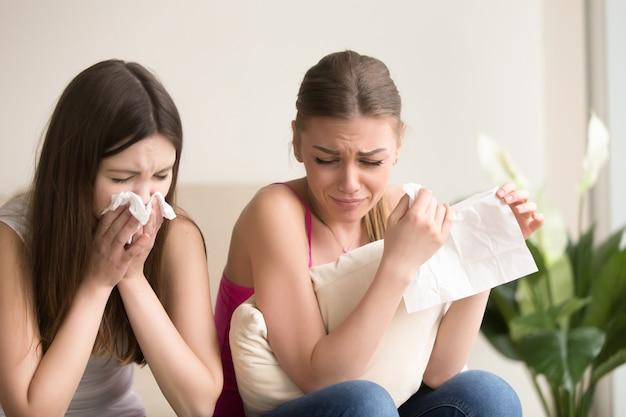 Twee jonge vrouwenvrienden die samen thuis huilen Gratis Foto