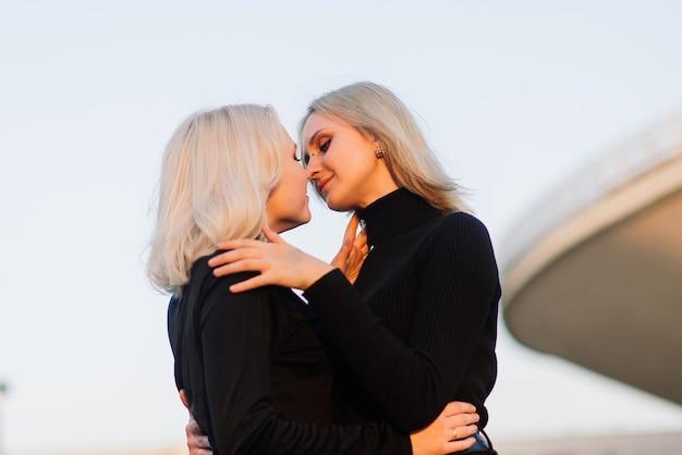 Twee jonge vrouwtjes zoenen buiten in de stad Premium Foto