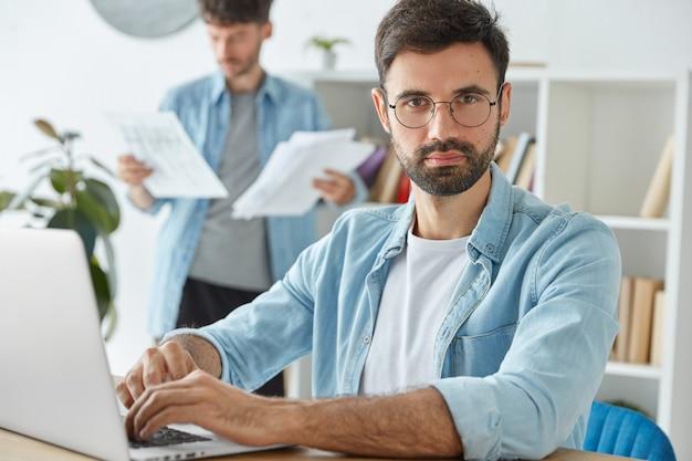 Twee jonge zakenlieden brengen productieve ochtend door op kantoor, ontwikkelen de bedrijfsstrategie, werken met laptop en zakelijke papieren Gratis Foto