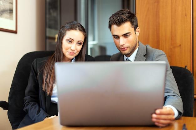 Twee jonge zakenpartners plannen of ideeën tijdens bijeenkomst bespreken Premium Foto