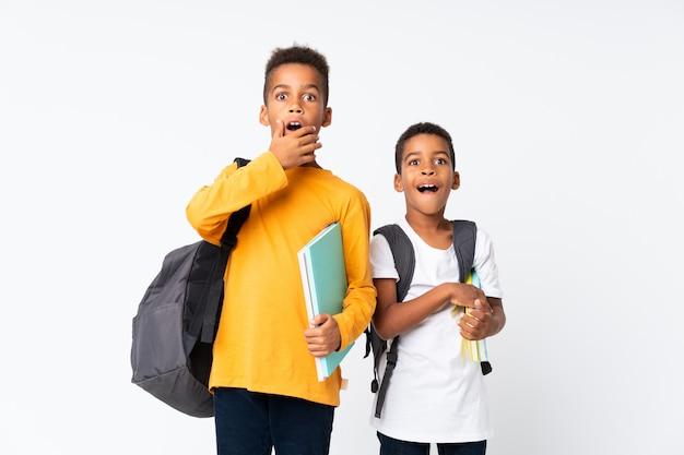 Twee jongens afrikaanse amerikaanse studenten over geïsoleerd wit die verrassingsgebaar doen Premium Foto