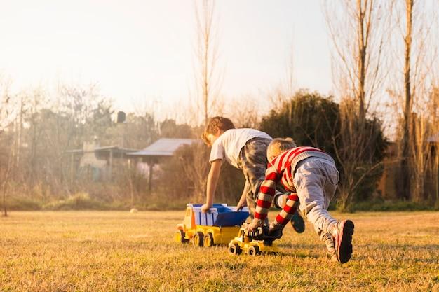 Twee jongens die met stuk speelgoed voertuigen spelen op het groene gras Gratis Foto