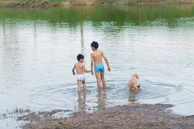 Twee jongens van verschillende leeftijden en honden gaan zwemmen in de rivier Premium Foto