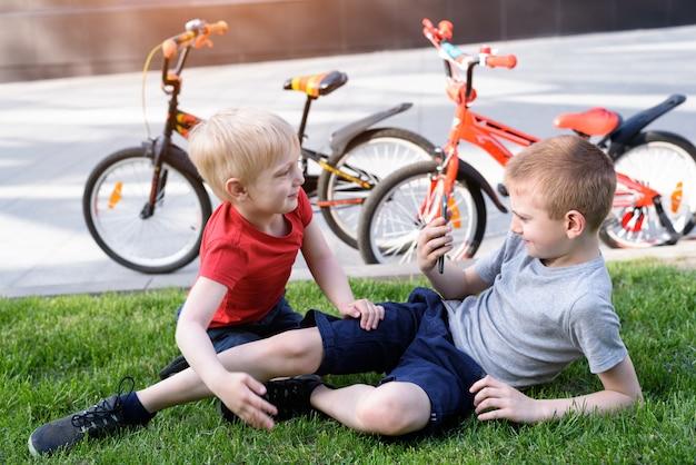 Twee jongens worden gefotografeerd op een smartphone terwijl ze op het gras zitten. rust na het fietsen, fietsen op de achtergrond Premium Foto