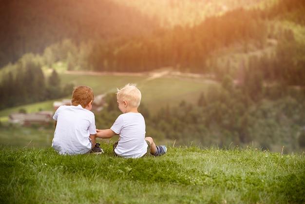 Twee jongens zitten op de heuvel Premium Foto