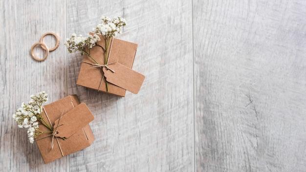 Twee kartonnen geschenkdozen met trouwringen op houten gestructureerde achtergrond Gratis Foto
