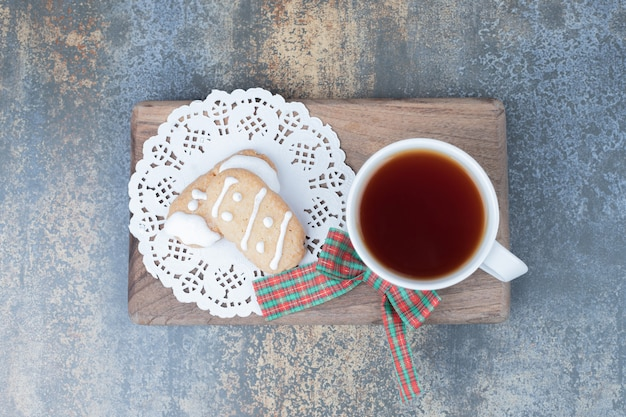 Twee kerstkoekjes en kopje thee op een houten bord. hoge kwaliteit foto Gratis Foto