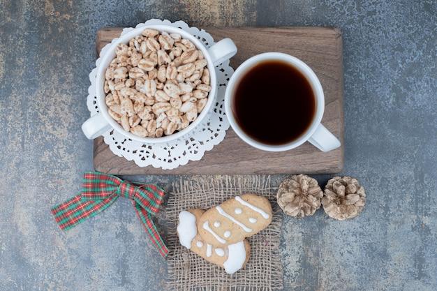 Twee kerstkoekjes, kopje thee en zoete pinda's op een houten bord. hoge kwaliteit foto Gratis Foto