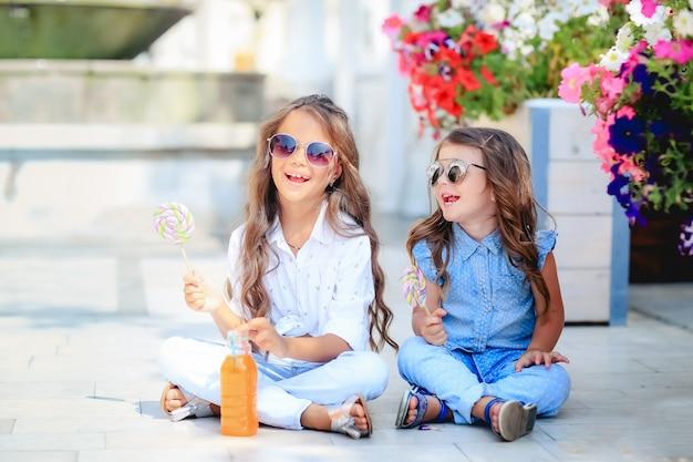 Twee kinderen die snoep eten, loly-pop op straat Premium Foto